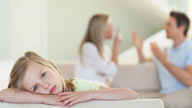 Niña triste mientras sus padres discuten