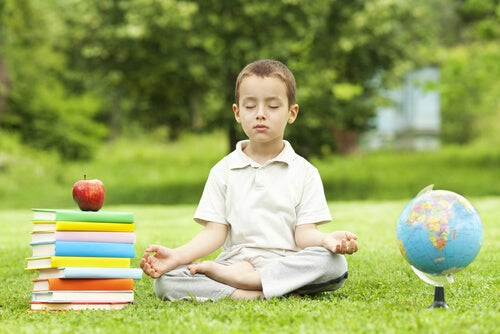boy practicing meditation with school books beside him