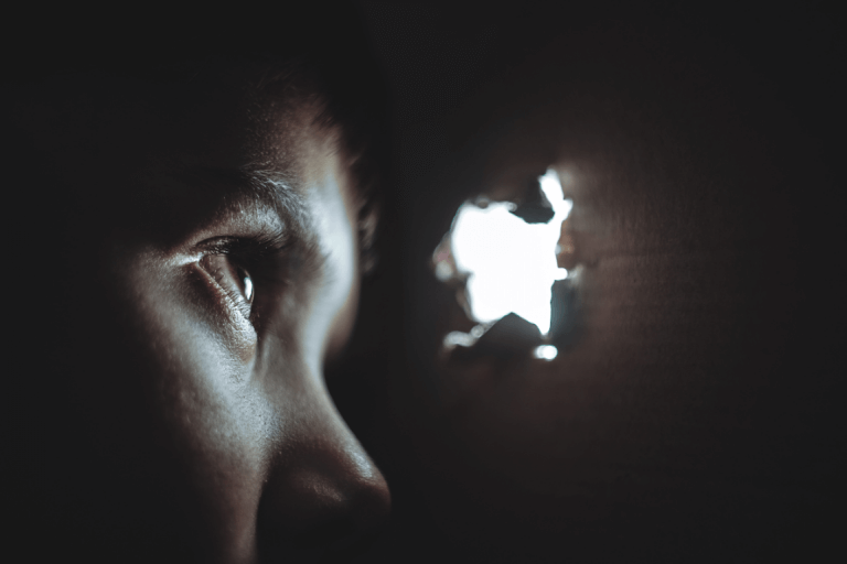 Niño mirando por un agujero