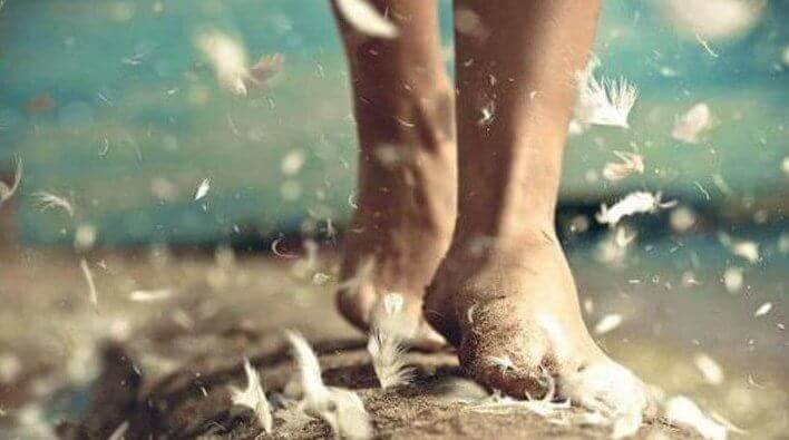 Pies entre plumas simbolizando la felicidad en pequeños actos