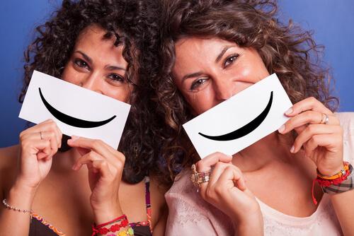 Amigas sujetando un cartel con una sonrisa