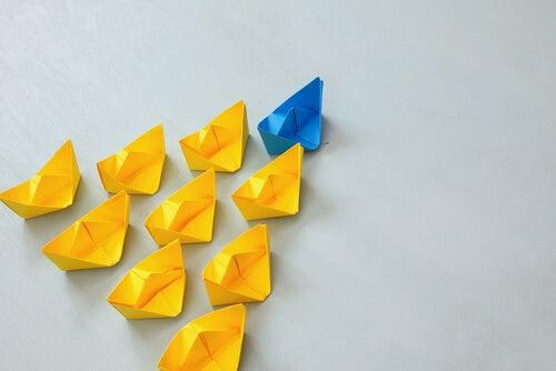 Barcos de papel amarillos siguiendo a un barco de papel azul