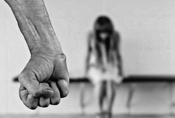 Brazo de un hombre y mujer sentada con miedo por la violencia