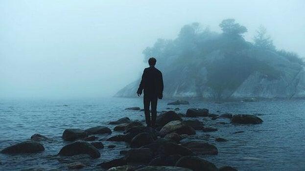 chico sobre rocas en una playa representando a una persona sensible