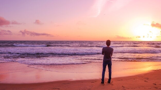 chico solitario mirando la playa al amanecer pensando en las fases del estrés