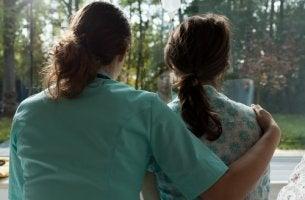 Enfermera abrazando a una mujer con cáncer de mamá mientras miran por la ventana