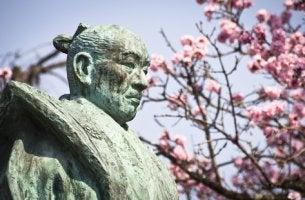 Figura de viejo samurái con árbol de flores rosas
