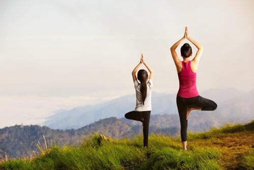 Hija haciendo yoga con su madre a través del aprendizaje vicario