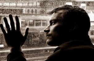 hombre inteligente con la mano sobre cristal con lluvia