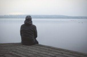 Hombre con trastorno de la personalidad esquizoide sentado mirando un lago