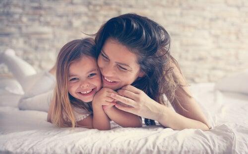 Madre con su hija encima de la cama