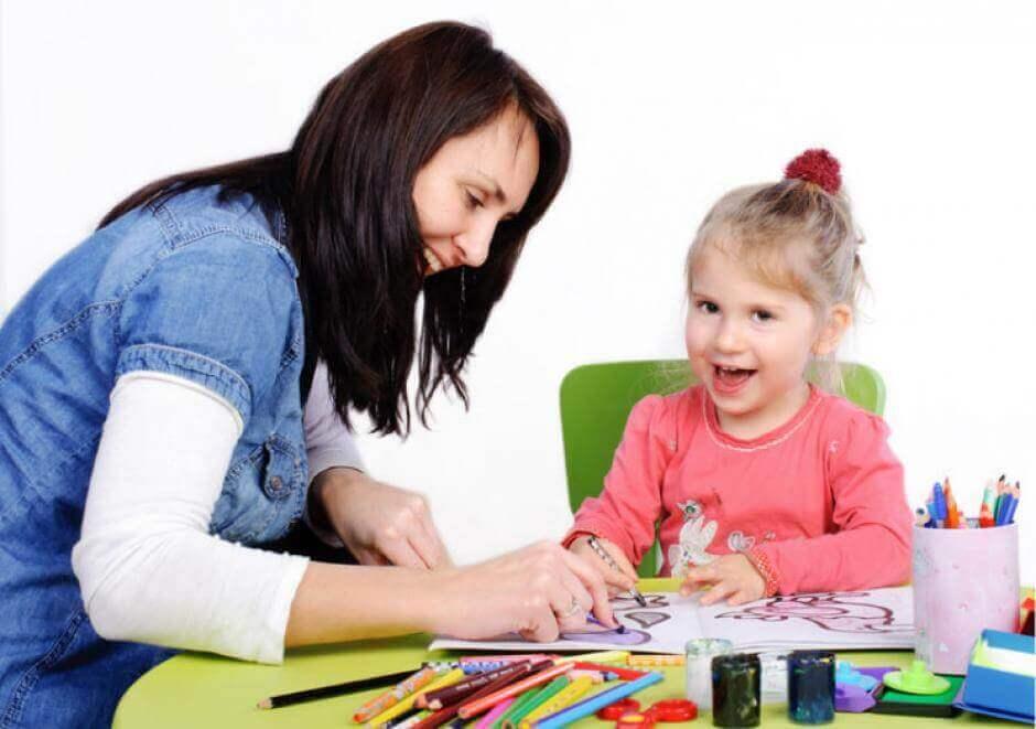Mujer coloreando con una niña