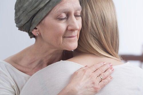 Mujer con cáncer de mama abrazando a su hija sufriendo el efecto del quimiocerebro