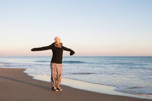 Mujer con cáncer en la playa con los brazos abiertos