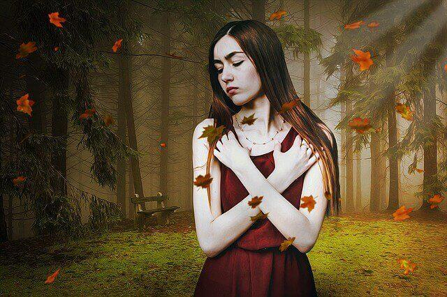 Mujer sintiendo inseguridad mientras se agarra los hombros