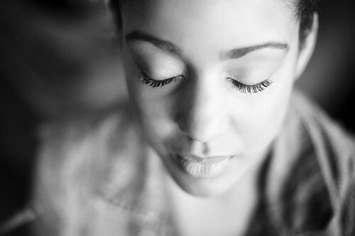 Mujer con los ojos cerrados para sentir sus emociones