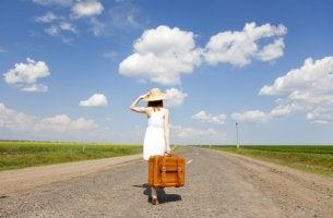 Mujer con maleta por la carretera