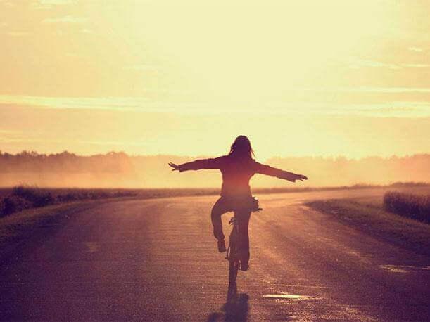 Mujer disfrutando de su felicidad en bicicleta