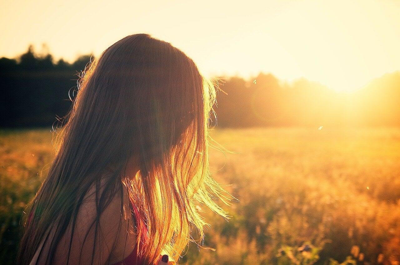 Mujer pensando en la felicidad mientras pasea por el campo