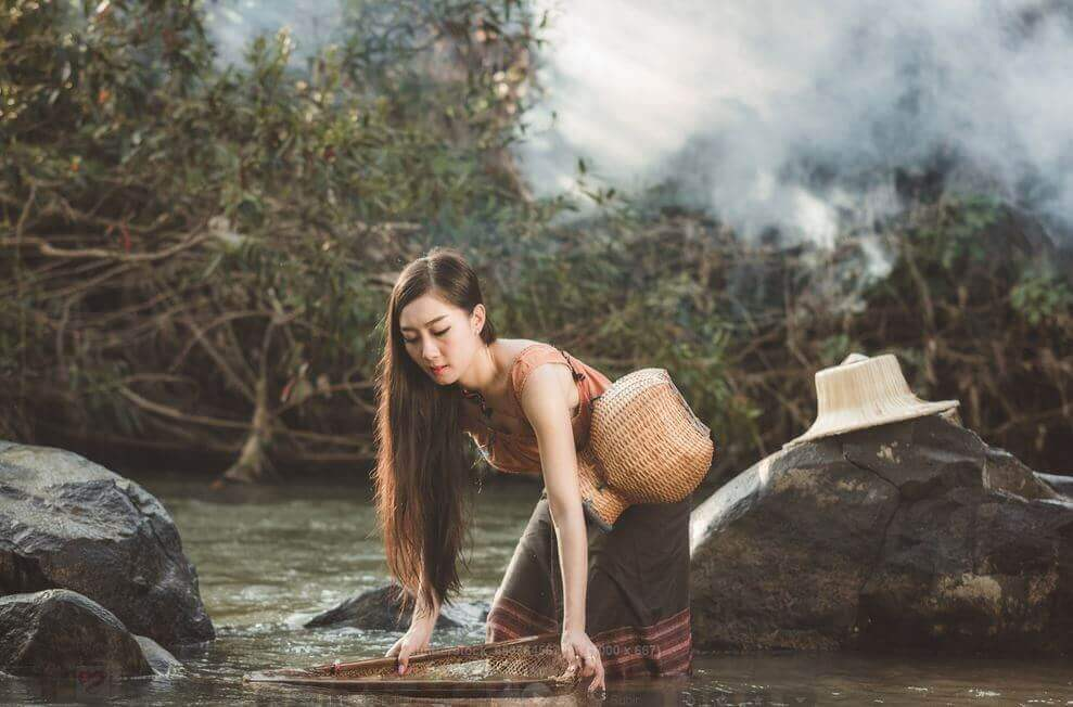 Mujer en el lago pensando en las nubes grises
