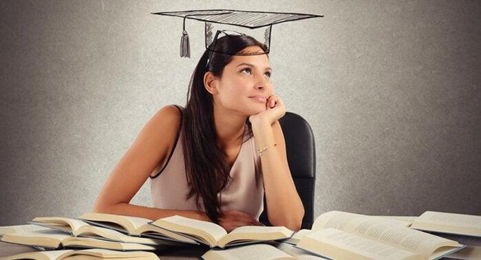 Mujer estudiando con muchos libros