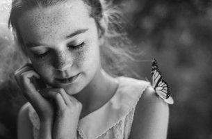 niña con una mariposa en el hombro