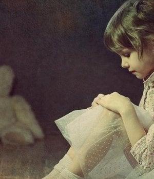 niña sentada frente a un osito representando el apego evitativo