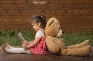Niña leyendo de espaldas a un oso de peluche