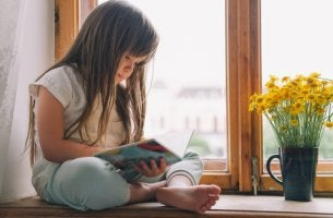 Niña leyendo un libro al lado de la ventana