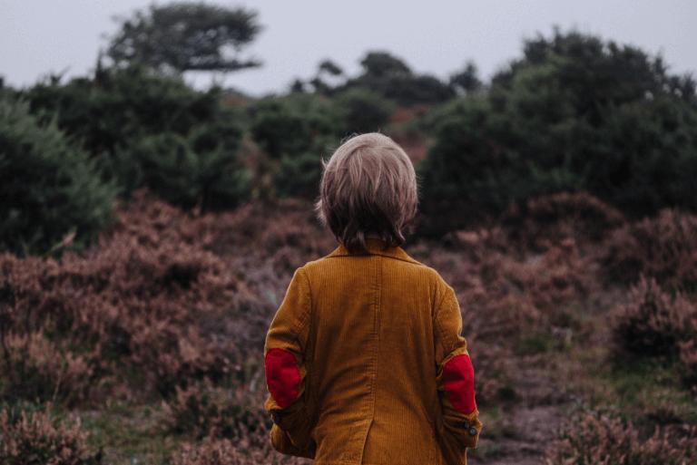 Niño solo con depresión de espaldas en el campo