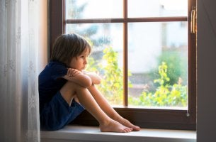 Niño triste al lado de la ventana