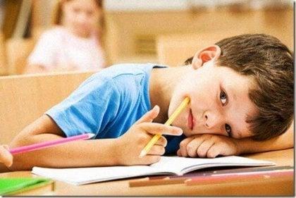 Niño con lápiz en la mejilla