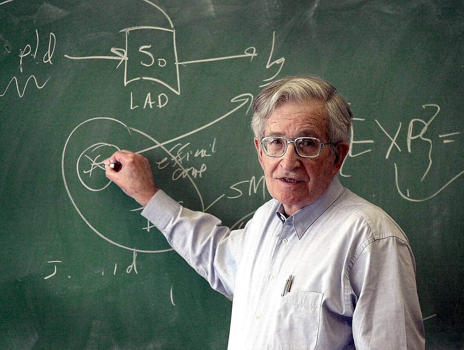 Noam Chomsky writing on a chalk board