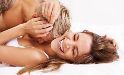 Pareja riéndose en la cama por tener sexo frecuente