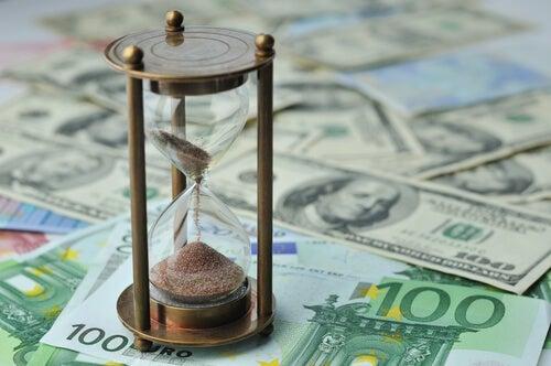 Reloj de arena sobre dinero representando las teorías de Joseph E. Stiglitz