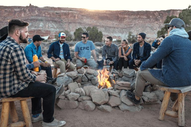 Amigos reunidos conversando alrededor de una hoguera