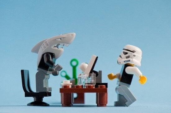 Jefe tóxico con cabeza de tiburón enfadado con su empleado