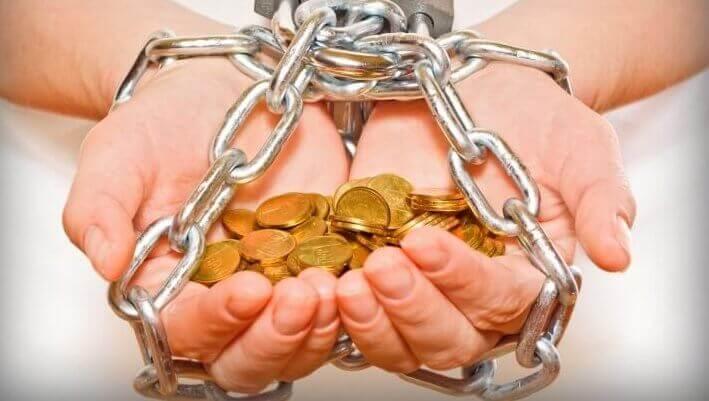 Manos con monedas atadas