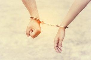 Manos de una pareja esposadas simbolizando relaciones adictivas