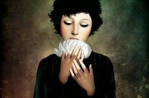 mujer con flor blanca en las manos experimentando gratitud