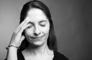 Mujer con la mano sobre la cabeza por problema de amnesia anterógrada