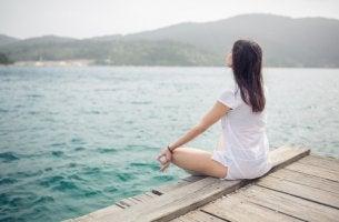 Mujer meditando frente al río