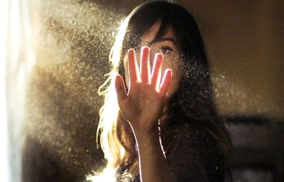 mujer que pone la mano en haz de luz experimentando presentimientos