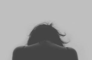 Mujer triste mirando hacia el suelo por situación de maltrato
