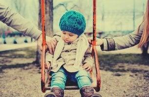 niño en el columpio con sus padres divorciados