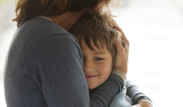 Niño feliz abrazado por su madre