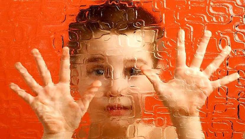 niño con esquizofrenia infantil que pone manos sobre cristal