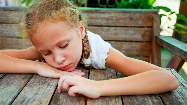 Niña con depresión apoyada sobre una mesa