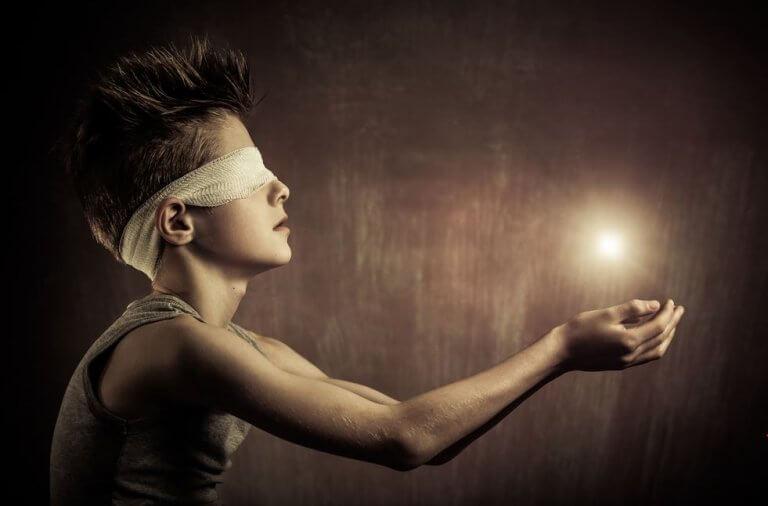 Niño con una luz sobre sus manos