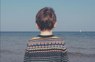 Niño de espaldas mirando al mar